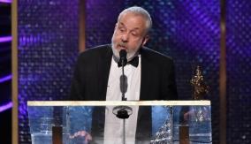 Leigh accepts his award